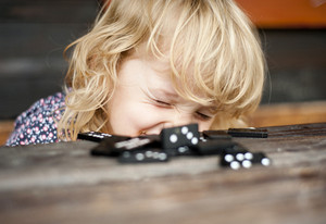 Cute little girl playing with black domino ouside the house.