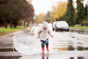 Cute little girl playing with transparent umbrella in town on a rainy day.