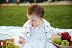 Cute little girl sitting and choosing fruits on picnic