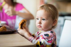 Cute little girl sitting at the kitchen table eating croissant