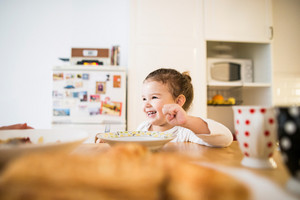 Cute little girl sitting at the table in the kitchen, eating breakfast