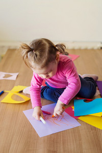 Cute little girl sitting on a floor at home drawing on colorful papers