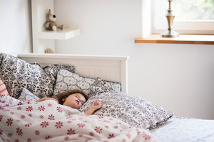 Cute little girl sleeping in the afternoon in bed, surrounded by pillows and bedding sheets.