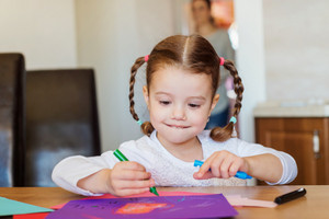 Cute little girl with braids at home drawing on colorful papers
