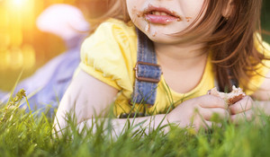 Cute little girl with chocolate face lying on a grass