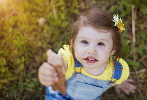 Cute little girl with chocolate face sitting on a grass