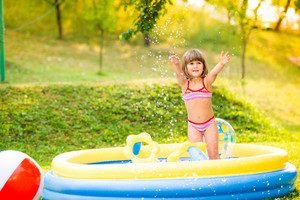 Cute little girl with colorful ball having fun in yellow garden swimming pool. Sunny summer day at the backyard