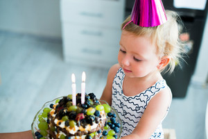 Cute little girl with her fruit birthday cake with two candles. Pink party hat on head.