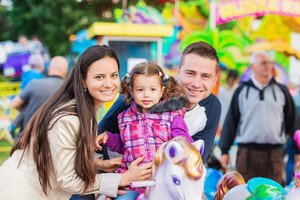 Cute little girl with her mother and father enjoying ride at fun fair, amusement park