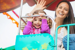 Cute little girl with her mother enjoying time at fun fair, amusement park