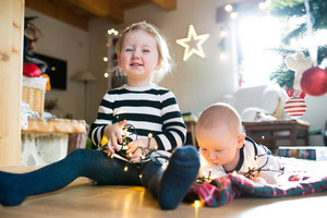 Cute little girl with his baby brother under Christmas tree lying on checked blanket entangled in chain of lights.
