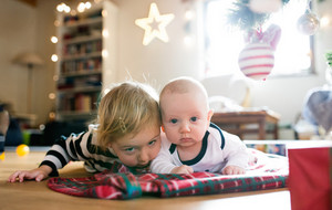 Cute little girl with his baby brother under Christmas tree lying on checked blanket.