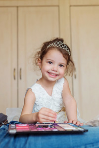 Cute little girl with princess crown smiling, playing with make up