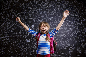 Cute little girl with scholl bag in front of big blackboard