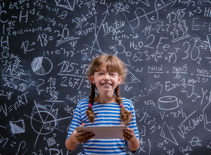 Cute little girl with tablet in front of big blackboard