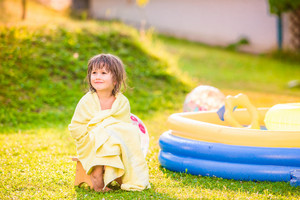 Cute little girl wrapped in towel sitting in the garden by the home swimming pool, sunny summer back yard