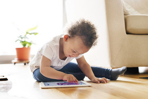 Cute little mixed-race girl with curly hair at home sitting on wooden floor playing game on tablet.