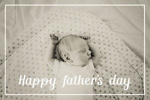 Cute little newborn baby boy lying on bed, sleeping, arms raised above head. Fathers day concept.
