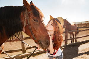 Cute lovely young woman cowgirl standing and kissing her horse