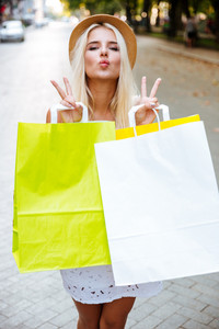 Cute lovely young woman in hat holsing shopping bags and sending a kiss