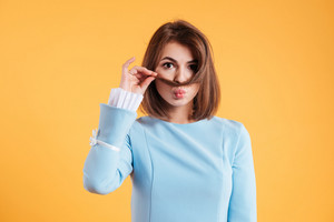 Cute lovely young woman making moustache with her hair over yellow background
