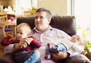 Cute newborn baby boy and his little brother relaxing at home with their father