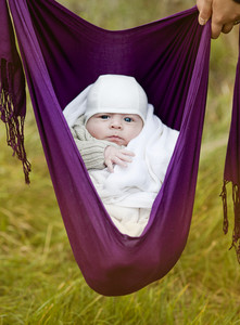 Cute newborn baby boy hanging in a baby sling outdoor