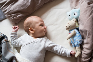 Cute newborn baby boy in gray onesie lying on bed, teddy bear toy next to him