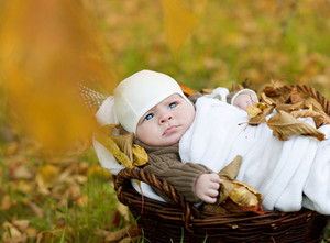 Cute newborn baby boy lying down in basket in autumn nature