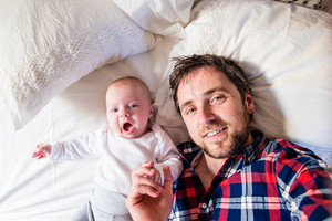 Cute newborn baby boy lying on a bed, next to his father