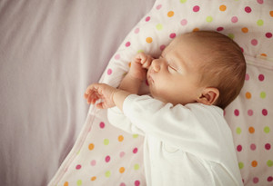 Cute newborn baby girl sleeping in bed at home