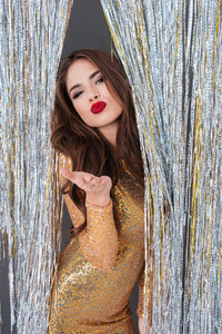 Cute playful young woman in golden dress standing and sending kiss in sparkling decorations