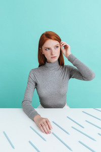 Cute redhead young woman sitting at the table with pencils over blue background