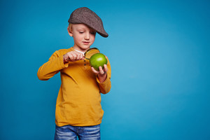 Cute schoolboy in casualwear and cap looking at green apple through magnifying glass