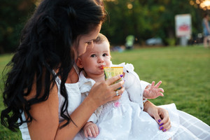 Cute small girl sitting and drinking juice with her mom outdoors