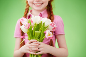 Cute smiling girl holding bunch of tulips