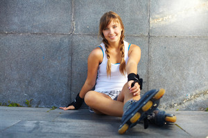 Cute teenage girl in roller skaters looking at camera
