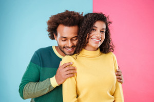 Cute tender african couple standing and hugging over pink and blue background