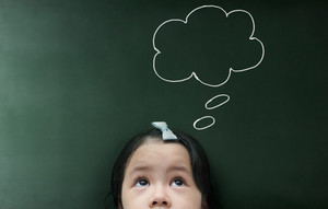 Cute thinking kid girl with empty bubble looking on the blackboard background.