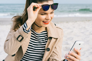 Cute woman on the beach in coat and sun glasses enjoys looking at the mobile phone screen