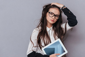Cute young Asian model in glasses holding tablet computer, straightens hair and looking at camera. Isolated gray background