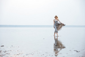 Cute young woman in long dress walking on the beach