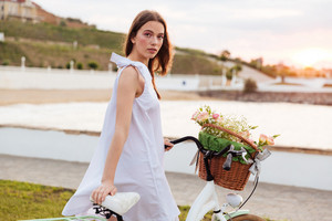 Cute young woman in white dress with bicycle standing on promenade