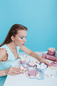 Cute young woman sitting at the table with plasic dishes and marshmallows over blue background