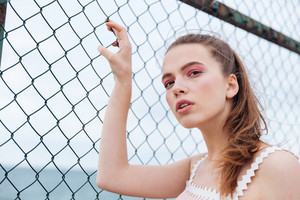 Cute young woman standing outdoors and touching chain link fence