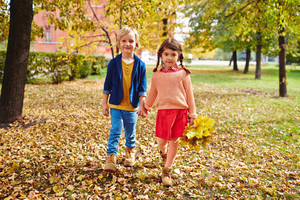 Cute youngsters looking at camera while taking walk in park