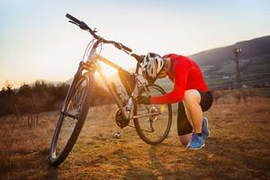Cyclist man repairing his mountain bike in sunny meadow