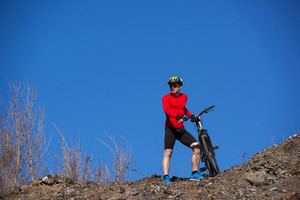 Cyclist man standing on top of a mountain with bicycle and enjoying valley view on a sunny day against a blue sky