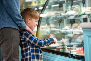 Dad and little son choosing and pointing at sweet cake in showcase