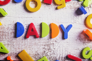 Daddy sign and colorful toys laid on wooden background.